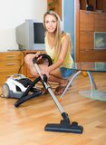 Blonde woman with vacuum cleaner Stock Image