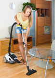Blonde woman with vacuum cleaner Stock Images
