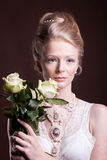 Blonde woman in victorian dress with roses in hands Stock Photo