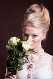 Blonde woman in victorian dress with roses in hands Stock Image