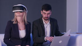 Blonde woman in vr headset discussing construction project with her partner holding blueprints in front of laptop stock video