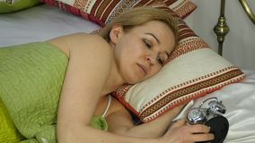 Blonde woman wakes up, looks at alarm clock and hides it under the pillow. slow motion stock video