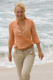 Blonde woman walking on the beach. #1 Royalty Free Stock Images