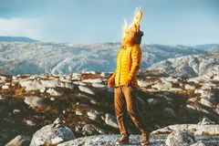Blonde Woman walking outdoor in mountains hair on wind. Travel Lifestyle emotional concept adventure outdoor vacations tourist girl wearing orange dawn jacket royalty free stock photography