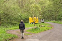 A blonde woman is walking towards an solated yellow caravan in the forest Germany, Europe royalty free stock photos