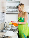 Blonde woman washing plates with sponge. In domestic kitchen royalty free stock photography