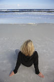 Blonde woman wearing black jumper, sitting on sandy beach, looking at horizon over sea, rear view, elevated view (tilt) Stock Photography
