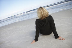 Blonde woman wearing black jumper, sitting on sandy beach, looking at horizon over sea, rear view (tilt) Stock Photos
