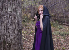 Blonde woman wearing black mantle in autumn forest Royalty Free Stock Image