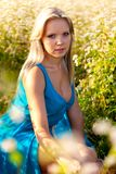 Blonde woman wearing blue dress on a field Stock Photos