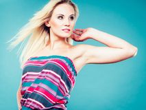 Blonde woman wearing colorful striped strapless shirt. Summer trendy fashionable outfit ideas concept. Blonde woman wearing colorful striped strapless shirt Royalty Free Stock Images