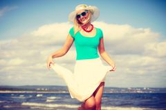 Blonde woman wearing dress walking on beach Royalty Free Stock Photography
