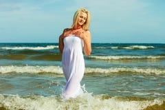 Blonde woman wearing dress walking in water Stock Photography