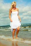 Blonde woman wearing dress walking in water Stock Photos