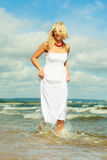 Blonde woman wearing dress walking in water Stock Image