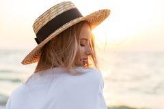 Blonde woman wearing hat outdoors at the beach. Image of cheerful cute blonde woman wearing hat outdoors at the beach looking aside Stock Photography