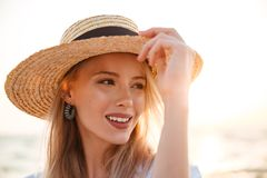 Blonde woman wearing hat outdoors at the beach. Image of cheerful cute blonde woman wearing hat outdoors at the beach looking aside Stock Images
