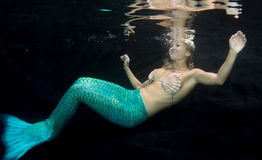 Blonde woman wearing a mermaid tail Stock Photo