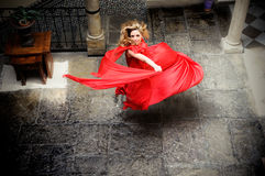 Blonde woman, wearing a red dress, jumping Stock Images
