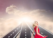 Blonde woman wearing red dress and twirling. Composite image of blonde woman wearing red dress and twirling on streets floating in the sky Stock Image