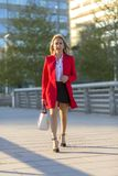 Blonde woman wearing red jacket and white handbag walking on the royalty free stock image