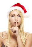 Blonde woman wearing santa\'s hat putting Stock Image
