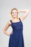 Blonde woman wearing short navy cocktail dress. Summer trendy fashionable outfit ideas concept. Blonde attractive woman wearing short blue cocktail dress Royalty Free Stock Photo