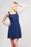 Blonde woman wearing short navy cocktail dress. Summer trendy fashionable outfit ideas concept. Blonde attractive woman wearing short blue cocktail dress Royalty Free Stock Images