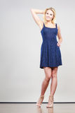 Blonde woman wearing short navy cocktail dress Stock Images