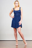 Blonde woman wearing short navy cocktail dress. Summer trendy fashionable outfit ideas concept. Blonde attractive woman wearing short blue cocktail dress and Stock Image