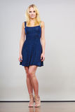 Blonde woman wearing short navy cocktail dress. Summer trendy fashionable outfit ideas concept. Blonde attractive woman wearing short blue cocktail dress and Royalty Free Stock Images
