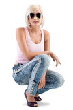 Blonde woman wearing sunglasses. Blonde woman fashion portrait wearing sunglasses and pink tank top over white Stock Photo