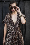 Blonde woman wearing sunglasses and leopard-skin dress. Beautiful blonde woman wearing sunglasses and a leopard-skin dress Royalty Free Stock Images