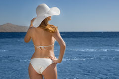 Blonde woman wearing white bikini and hat on beach Royalty Free Stock Photography