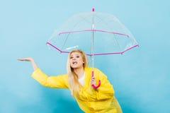 Woman wearing raincoat holding umbrella checking weather. Blonde woman wearing yellow raincoat holding transparent umbrella checking weather if it is raining Royalty Free Stock Photography