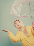 Woman wearing raincoat holding umbrella checking weather Stock Image