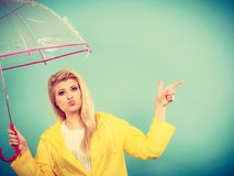Woman wearing raincoat holding umbrella pointing Stock Images