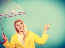 Woman wearing raincoat holding umbrella pointing. Blonde woman wearing yellow raincoat holding transparent umbrella checking weather if it is raining pointing Royalty Free Stock Image