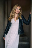 Blonde woman in white dress and black leather coat posing walking outdoors Stock Photo