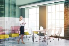 Blonde woman in white and green cafe royalty free stock photo