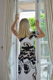 Blonde Woman by a Window. Blonde woman in an elegant summer dress standing by a window with a view to a garden Royalty Free Stock Photos
