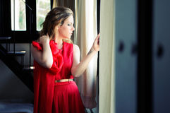 Blonde woman in window wearing a red dress. Portrait of a beautiful blonde woman in window wearing a red dress Royalty Free Stock Image
