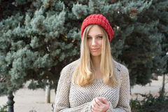 Blonde woman in winter, con red knitted hat, fir trees Royalty Free Stock Image