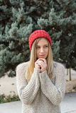 Blonde woman in winter, con red knitted hat, fir trees Royalty Free Stock Photography
