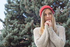 Blonde woman in winter, con red knitted hat, fir trees Royalty Free Stock Photos