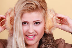 Blonde woman in winter earmuffs and jacket. Royalty Free Stock Photos