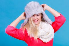 Blonde woman in winter furry hat. Accessories and clothes for cold days, fashion concept. Happy blonde woman in winter warm furry hat in russian style Royalty Free Stock Photos