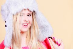 Blonde woman in winter furry hat. Accessories and clothes for cold days, fashion concept. Happy blonde woman in winter warm furry hat in russian style Stock Photography