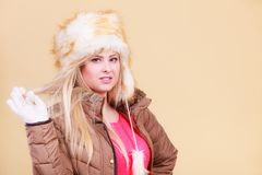 Blonde woman in winter furry hat. Accessories and clothes for cold days, fashion concept. Blonde woman in winter warm furry hat in russian style Royalty Free Stock Photo