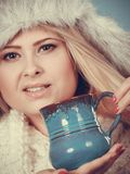 Blonde woman in winter furry hat drinking Royalty Free Stock Photography
